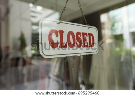 Close up shot of a closed sign hanging up on the glass door.  #695295460