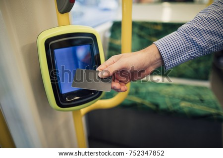 Close up shot of a commuting businessman scanning his travel card on a tram in Melbourne, Victoria.