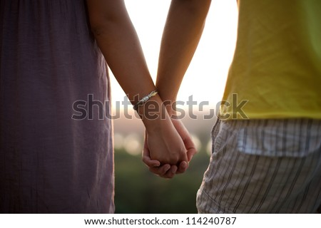 Close up shot of a couple holding hands.