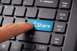 Close up shot of a finger clicking the SHARE button on a laptop keyboard