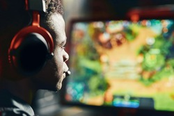 Close up shot of a focused african guy, professional cybersport gamer wearing headphones playing online video games