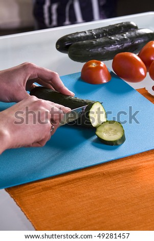Close up shot of a girl's hand cutting cucumbers