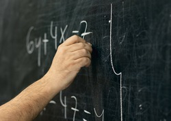 Close-up shot of a hand holding chalk and writing mathematical equations on the blackboard.