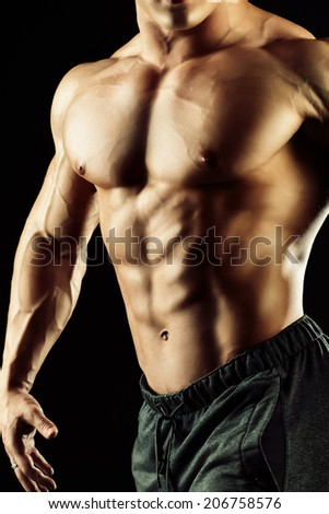 Close-up shot of a handsome muscular bodybuilder posing over black background.