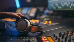 Close-up Shot of a Headphones lying on Mixing Board in Music Recording Studio. Successful Female Audio Engineer Creates Modern Song.