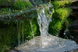 Close up shot of a homemade waterfall in a small backyard pond that filters water for a koi pond.