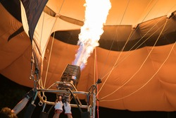 close up shot of a human hand burning inside the yellow hot air balloon in the dark night. A Hot Air Balloon burners in operation.
