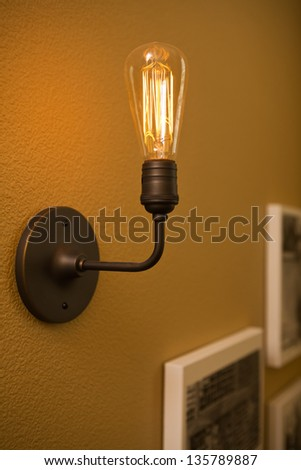 Close up shot of a light bulb/vertical shot of a vintage illuminated light bulb in a home
