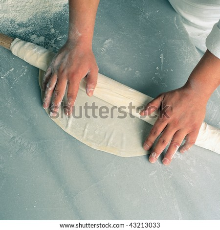 close up shot of a man rolling dough