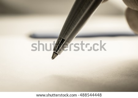Close up shot of a man's hand holding a ball point pen on the white paper