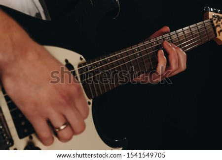 Close up shot of a man with his fingers on the frets of a guitar playing stock photo