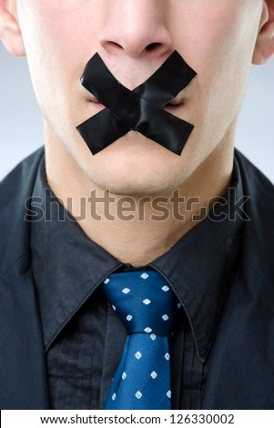 Close up shot of a man with tape over his mouth - censored speech concept