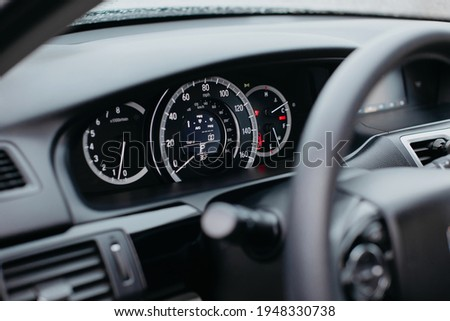 Close up shot of a miles speedometer in a car. Car dashboard. Dashboard details with indication lamps.Car instrument panel. Dashboard with speedometer, tachometer, odometer.