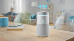 Close Up Shot of a Modern Silver Wireless Speaker Standing on a Table at Home with Voice Recording Hologram