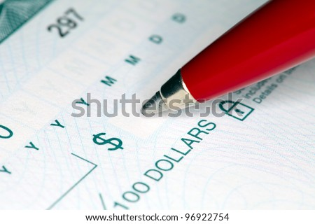 Close-up shot of a pen writing on a cheque. Shallow focus.
