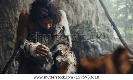 Close-up Shot of a Primeval Caveman Wearing Animal Skin Hits Rock with Sharp Stone, Makes First Primitive Tool for Hunting Animal Prey. Neanderthal Using Flint Rock. Dawn of Human Civilization.