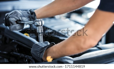 Close Up Shot of a Professional Mechanic Working on Vehicle in Car Service. Engine Specialist Fixing Motor. Repairman is Wearing Gloves and Using a Ratchet. Modern Clean Workshop.
