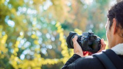 Close-up shot of a professional photographer, taking pictures in the woods. Man photoshooting in the park on a bright sunny autumn day. Copy space on the left.