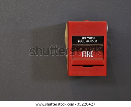 Close-up shot of a red fire alarm against a grey painted wall