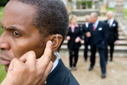 Close up shot of a senior businessman wearing an earpiece to aid his hearing standing with his colleagues walking towards him in the background