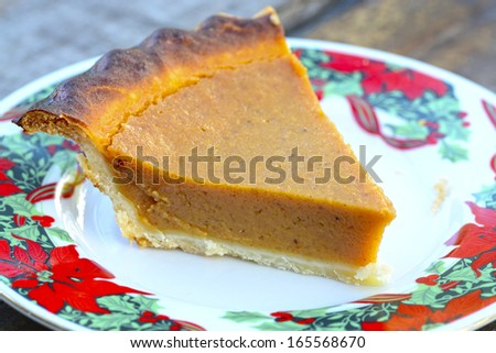 Close up shot of a slice of pumpkin on a holiday plate over a wooden table