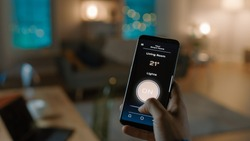 Close Up Shot of a Smartphone with Active Smart Home Application. Person is Tapping the Screen To Turn Lights On/Off in the Room. It's Cozy Evening in the Apartment.