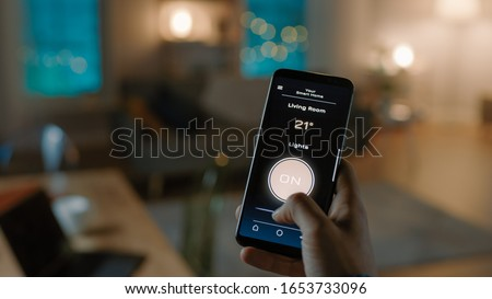 Close Up Shot of a Smartphone with Active Smart Home Application. Person is Tapping the Screen To Turn Lights On/Off in the Room. It's Cozy Evening in the Apartment. Foto stock ©