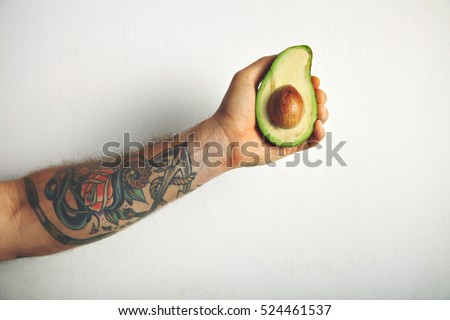 Close up shot of a tattooed man's arm with a half of ripe fresh avocado isolated on white #524461537