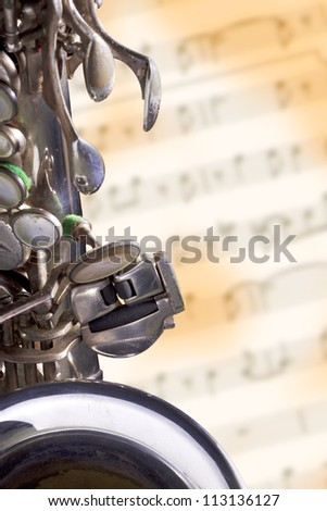 Close up shot of a vintage silver alto saxophone on blur grunge music sheet background