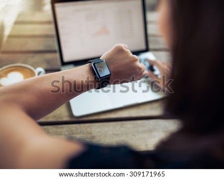 Close up shot of a woman checking time on her smartwatch. Female sitting in cafe with a laptop and cup of coffee. #309171965