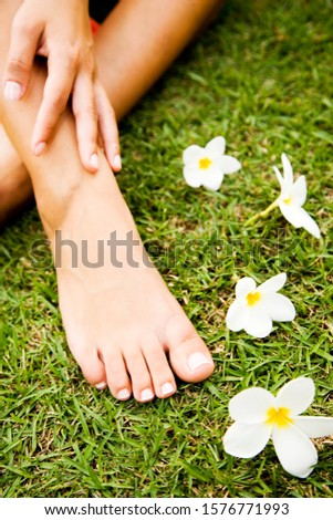 Close up shot of a woman's feet in a tropical setting with frangipani.