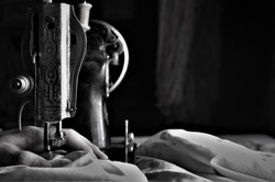 close up shot of a woman's hands, who is engaged in sewing in a small factory, a seamstress wants to make a summer dress for women, a needle and a thread falls on the fabric