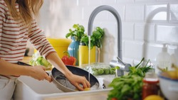 Close Up Shot of a Woman Washing a Frying Pan with a Cleaning Liquid Under Tap Water. Using Dishwasher in a Modern Kitchen. Natural Clean Diet and Healthy Way of Life Concept.