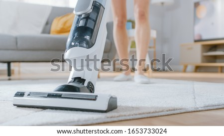 Close Up Shot of a Young Beautiful Woman in Jeans Shirt and Shorts Vacuum Cleaning a Carpet in a Bright Cozy Room at Home. She Uses a Modern Cordless Vacuum. She's Happy and Cheerful. Stockfoto ©