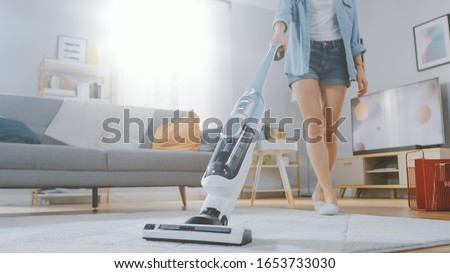 Close Up Shot of a Young Beautiful Woman in Jeans Shirt and Shorts Vacuum Cleaning a Carpet in a Bright Cozy Room at Home. She Uses a Modern Cordless Vacuum. She's Happy and Cheerful.