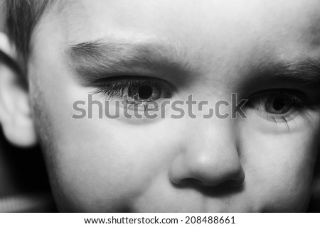 close up shot of a young boys face not looking happy as if hes about to cry