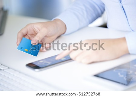 Close-up shot of a young businesswoman holding bank card in her hand while using smartphone app to log in her bank account.  #512752768