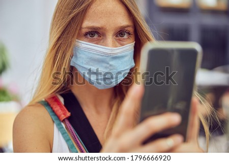 Close up shot of a young woman with freckles wearing a face mask is holding a smartphone while looking at the camera Stockfoto ©