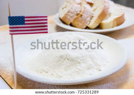 Close-up shot of american flag and flour in a plate. Slices of bread on the blurred background #725331289