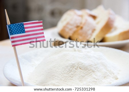 Close-up shot of american flag and flour in a plate. Slices of bread on the blurred background #725331298