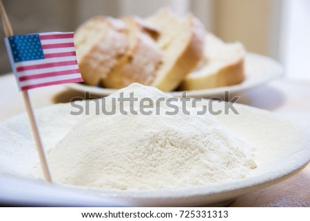 Close-up shot of american flag and flour in a plate. Slices of bread on the blurred background #725331313