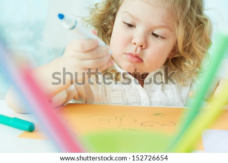Close-up shot of an adorable little girl being absorbed in drawing