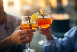 Close up shot of an young carefree romantic couple in love is drinking and cheering with cool alcohol cocktails while enjoying a happy hour time together in city center bar on a weekend in a sunny day