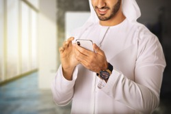 Close up shot of Arab Middle East man using smart mobile phone device browsing the internet or reading emails wearing Kandura and Ghutra