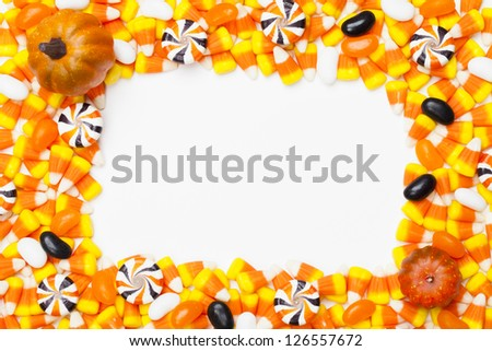 Close-up shot of arranged candy corns and pumpkins. #126557672