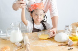 Close up shot of Asian little girl making bakery with mom with happiness , Select focus on face