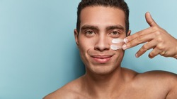 Close up shot of attractive man with healthy skin, applies cream for anti wrinkle or anti aging, cares of body, poses naked or shirtless, isolated over blue background with free space for your text