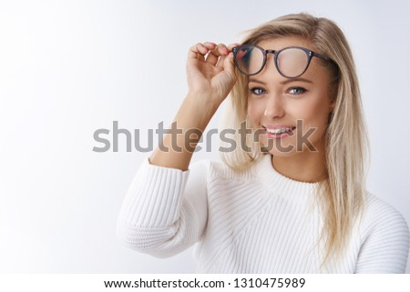 Close-up shot of attractive young and happy european female in sweater taking off glasses looking delighted with pure upbeat smile promoting eyewear feeling good in new frames over white wall