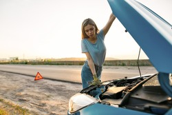 Close up shot of attractive young woman looking under the hood of her broken car while standing alone after car breakdown on the road side, Horizontal shot