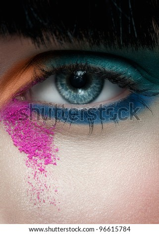 Close-up shot of beautiful female blue eye with bright colorful makeup - stock photo